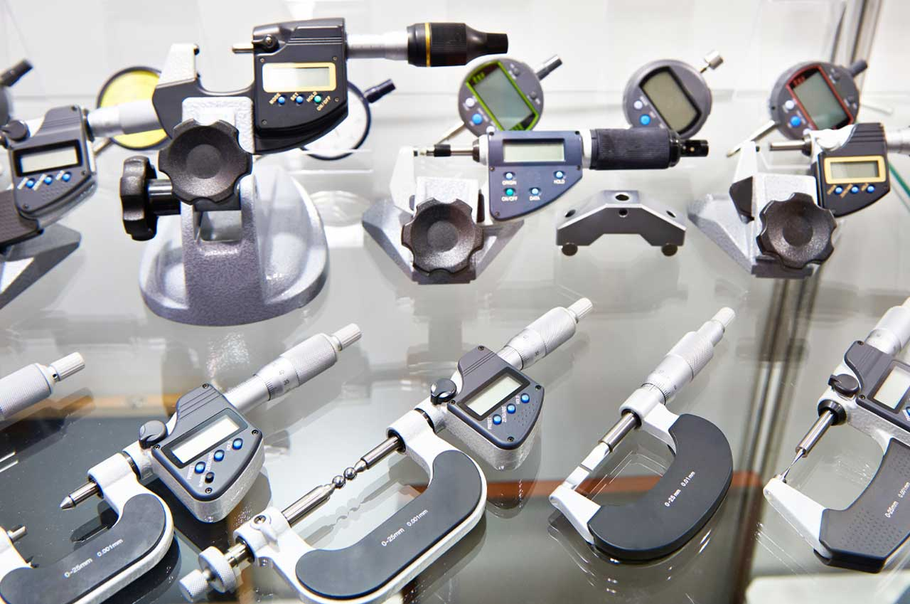 Digimatic and mechanical micrometers displayed on glass surface