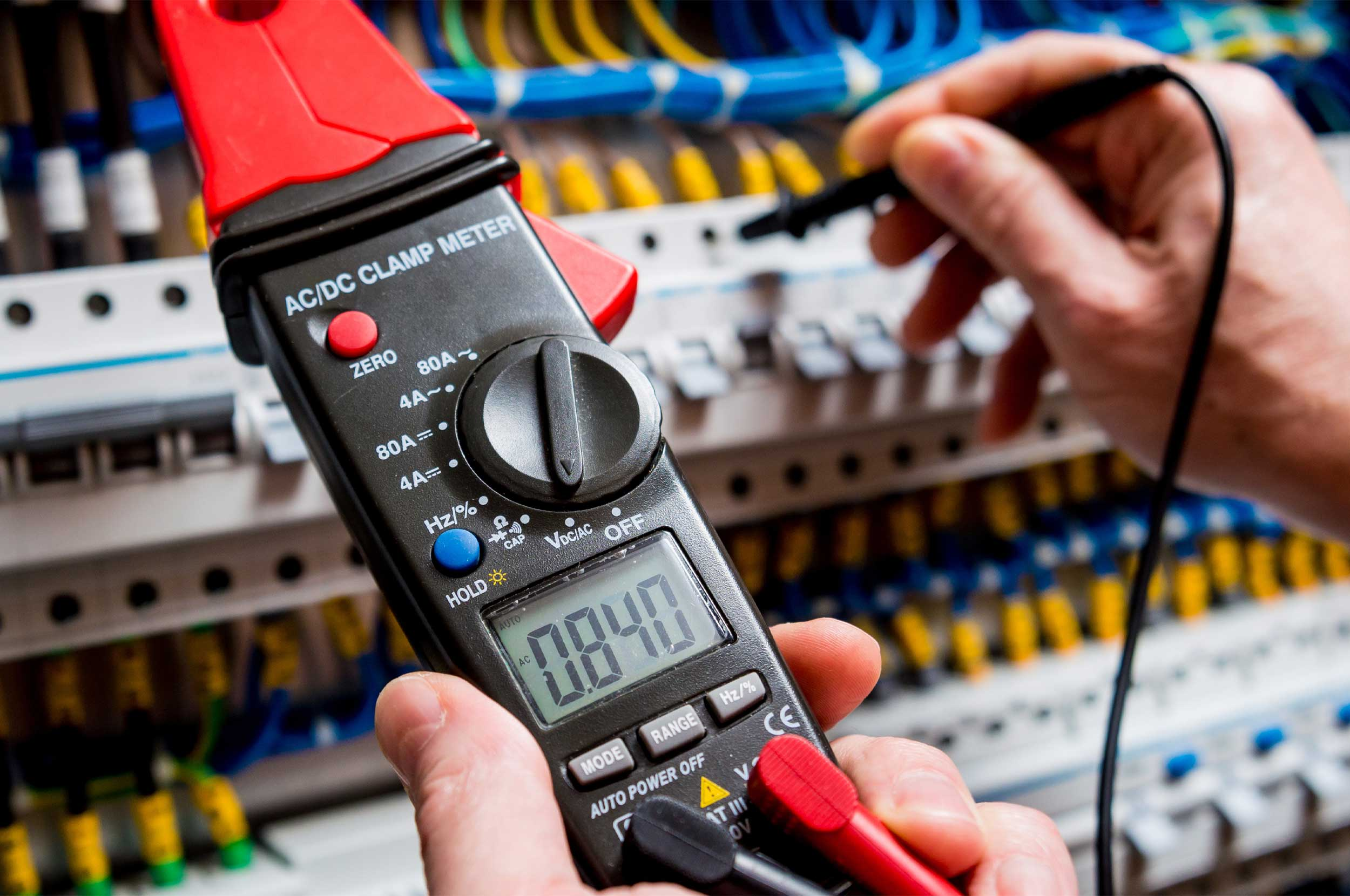 Multimeter tester being used to show electrical measurements.
