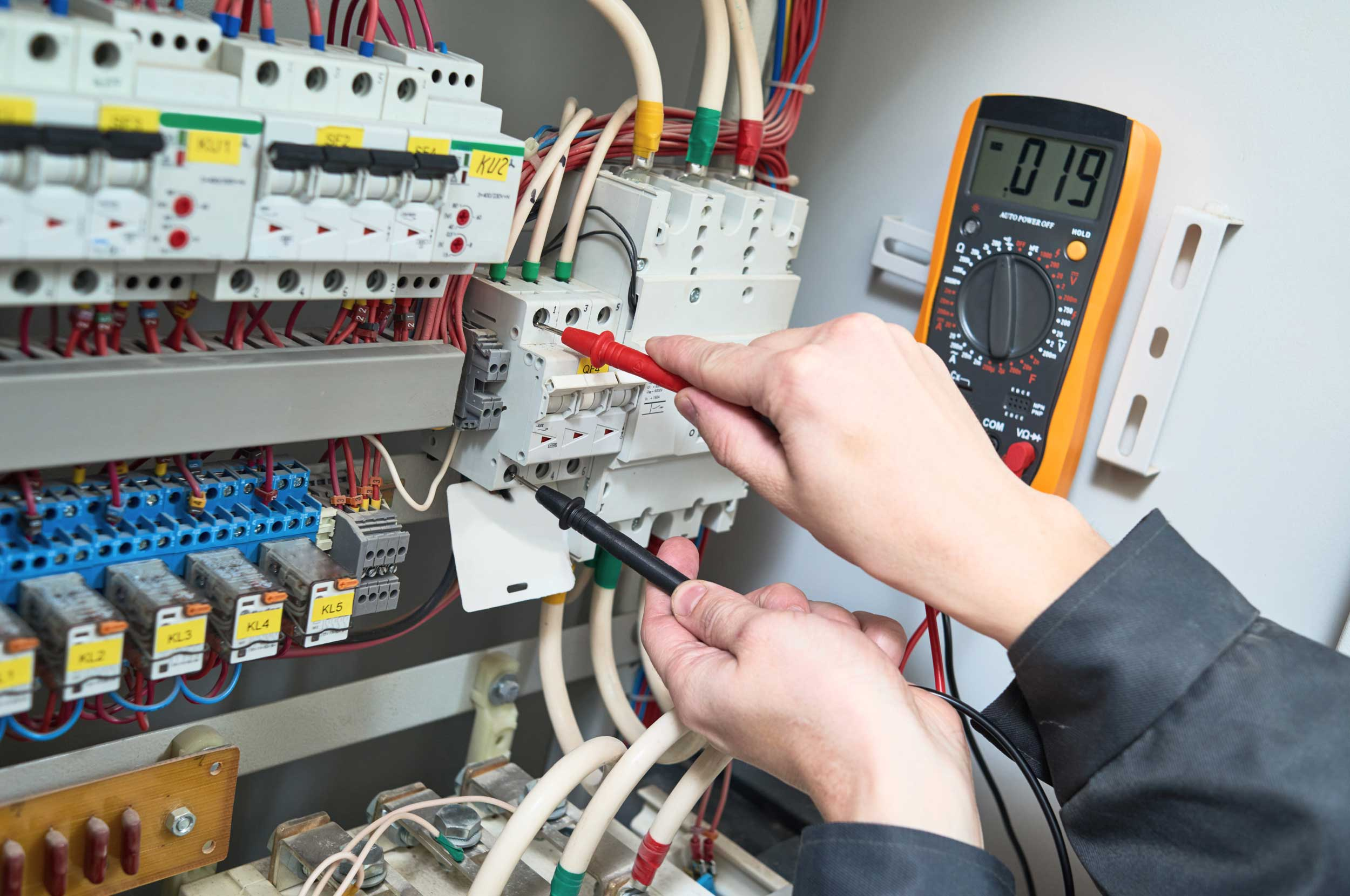 Electrician measures with multimeter tester